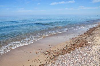 morze Bałtyckie z kamienistą plażą i delikatnymi falami przelewającymi się na brzeg